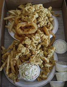 """Fried Clams_ are made by deep frying soft-shell clams that have been dipped in batter. Fried clams are an iconic food, """"to New England what barbecue is to the South"""". They tend to be served at seaside clam shacks (roadside restaurants). For a lighter meal, a clam roll is made by piling clams into a hot dog bun. Tartar sauce is the usual condiment."""