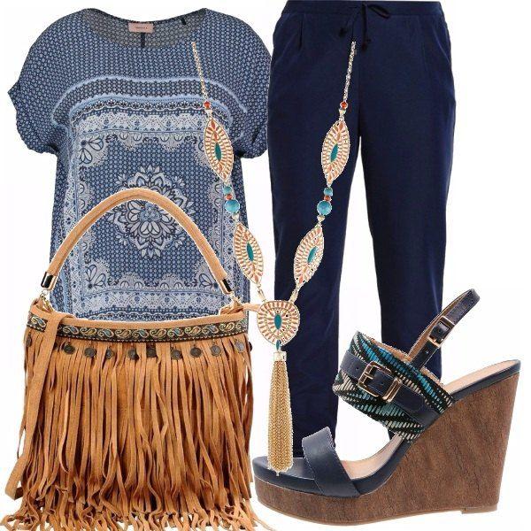 Blusa blu con fantasie in diverse tonalità dei blu, pantaloni con coulisse in blu navy e collana che accompagna. Borsetta con frange color cuoio e sandali con zeppa in blu e fantasia colorata.