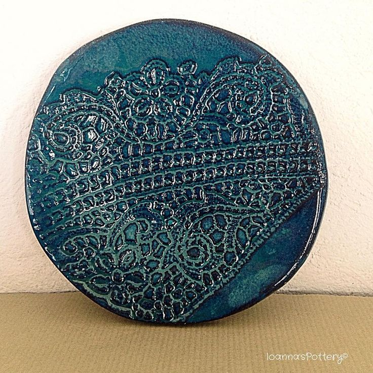 Deep petrol blue glossy glaze on a beautiful hand built plate with lace pattern surface from black clay.