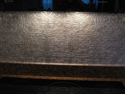 Fake-It Frugal: Fake Punched Tin Backsplash. It's textured wallpaper that's painted with metallic paint and coated in polyurethane. This link gives pictures and instructions.