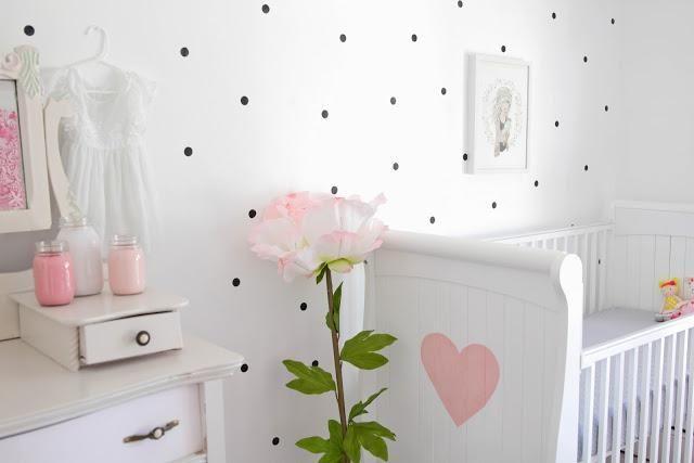 Una habitación infantil decorada en rosa y lunares