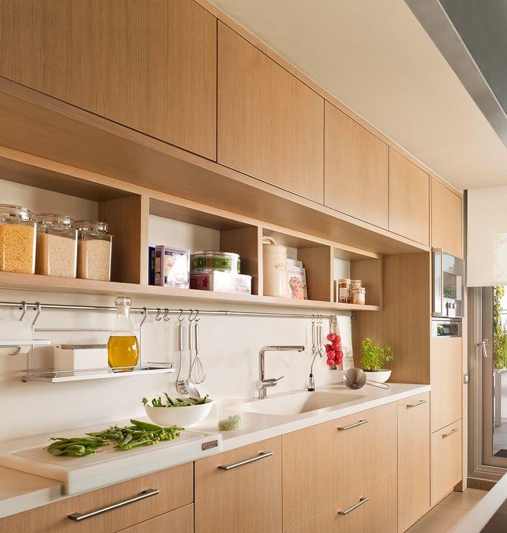 Cocina con muebles hasta el techo de madera y una zona de baldas. Si concentras el almacenaje en una sola pared liberas el resto de espacio de la cocina. Aquí se ha aprovechado cada centímetro: el armario tiene módulos altos y bajos, una estantería abierta y una barra para colgar.