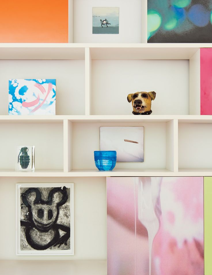 In the living area, a large shelf unit displays work by Marcel Dzama, David Mramor, Michael Ballou, Joyce Pensato, Cady Noland, and Mary Heilmann.