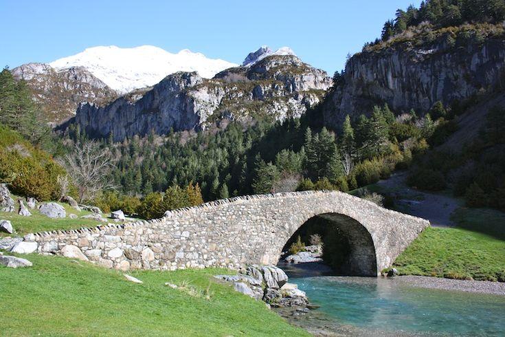 Bujaruelo Huesca A aproximadamente una hora de Ainsa y en pleno Pirineo de Huesca, se encuentra el idílico Valle de Bujaruelo. Montañas escarpadas, impresionantes cascadas, ríos de una agua azul esmeralda, prados verdísimos, ¡y hasta un puente de piedra! Con este tremendo paisaje, incluso las viajeras más urbanas nos rendimos a los encantos de la naturaleza.