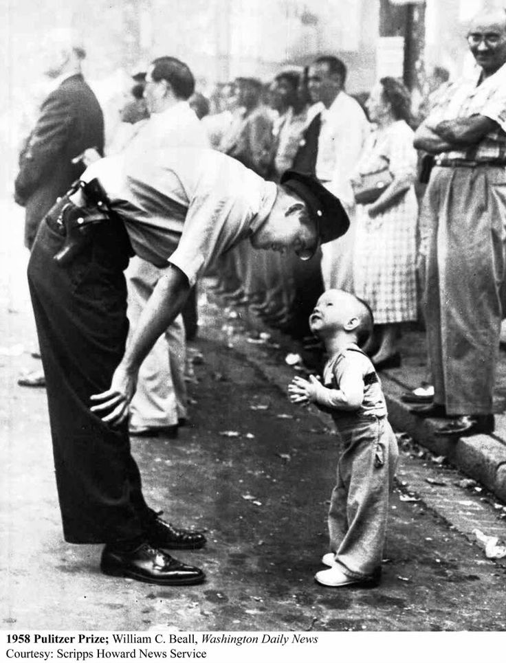 A policeman patiently reasoning with a two-year-old boy trying to cross a street during a parade 1958