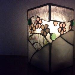 □送料無料□❤この作品は、受注制作品となっております。ご入金確認後、制作に入ります。 制作のお時間は、7日~10日程頂きます。ステンドグラス◆人感センサーランプ◆「JAPAN」ステンドグラス製の、人感センサーランプのカバーです。「桜」、「扇子」、「川の流れ」、をモチーフに「日本の美」を表現してみました。天面に桜色の美濃和紙を硝子で挟み込んであります。続き柄で、水の流れをイメージし、そこに、桜の花びらを舞わせてみました♪輸入硝子と、「和紙」がコラボした、四角柱の和風の雰囲気のランプです♪◆お誕生祝い、新築祝い、母の日、敬老の日、海外の方向けギフトetc・・・様々な、シーンの贈り物として、喜んで頂けるかと思います♪^^◆センサーランプはアルカリ単2電池4本で点灯する物ですのでいざという時の、防災用品としても備えて置かれると役に立ちますよ。◆サイズ   10.5cm×10.5cm×17cm※ 扇子部分に使用した硝子(ブルザイ社製)は、一枚の硝子で同じ柄が出にくいので、一点毎にピンクと緑色の模様や、縦筋のある無しや向きなど、模様の...