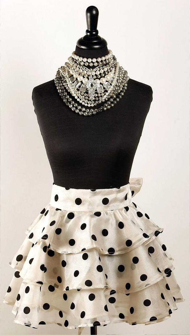 The ivory and black Faith cocktail apron from Heavenly Hostess is a flouncy concoction of polka-dotted organza ruffles. The suggested retail price is $80.