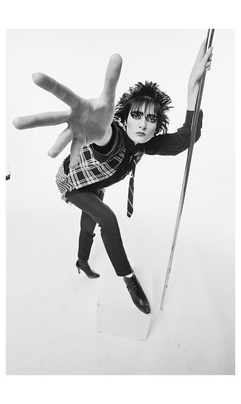 Siouxsie Sioux, singer with British punk band Siouxsie and the Banshees, poses holding onto a vertical stainless steel pole with her left hand, with her right arm outstretched towards the camera in...