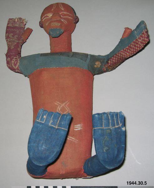 Sittande niombo med kropp och huvud i röd och blå textil, ansiktet bemålat, ögon och tänder av trä. Ett av ögonen saknas. På armarna sitter stycken av mönstrade tyger. Frisyr/hätta av mörkblåbommulsväv. Vid naveln har niombon magmålning. Sittande uppstoppad figur, klädd med rött och blått tyg. sträckt, de h andra sträckt uppåt. (Se foto i bildarkivet). Tänder och romboida ögon av påsatt trä (eha ögat saknas).