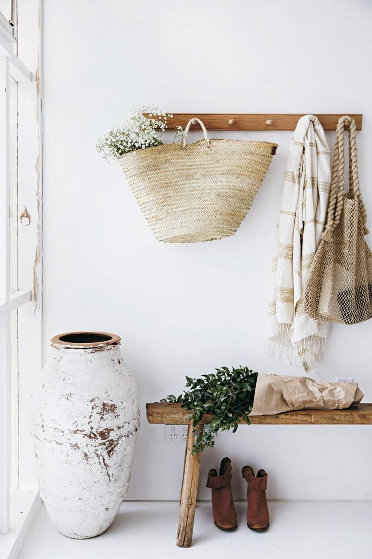 Sur cette photo j'aime : * Le grand vase façon ancien * La patère en bois avec un panier en osier accroché * Le feuillage dans le panier * le banc en bois simple