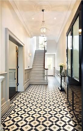 Perfect ceramic tiles for the floor in this grand, striking hallway. Love the grey panelled walls too.