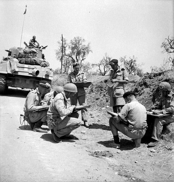 """Major Irwin, Officer Commanding """"C"""" Squadron, The Ontario Regiment, conferring with personnel of the squadron on the right flank of the Paterno front, Italy, August 3rd 1943."""