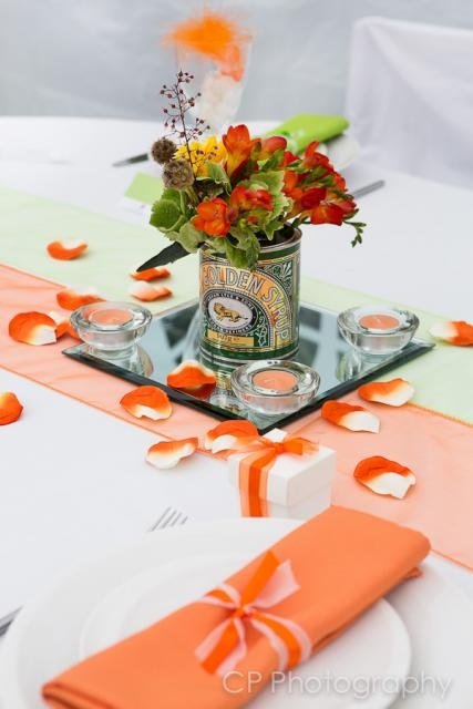 Tangerine orange organsa table runner, is great to add a splash of colour across a table.  Add faux rose petals and orange tea lights for extra decoration and detail.  Put a smile on your guests faces with a matching table favour.  Ribboned favour boxes with two heart chocolates or mint imperials inside.  Flowers by The White Horse Flower Company.  table accessories and styling by www.fuschiadesigns.co.uk.
