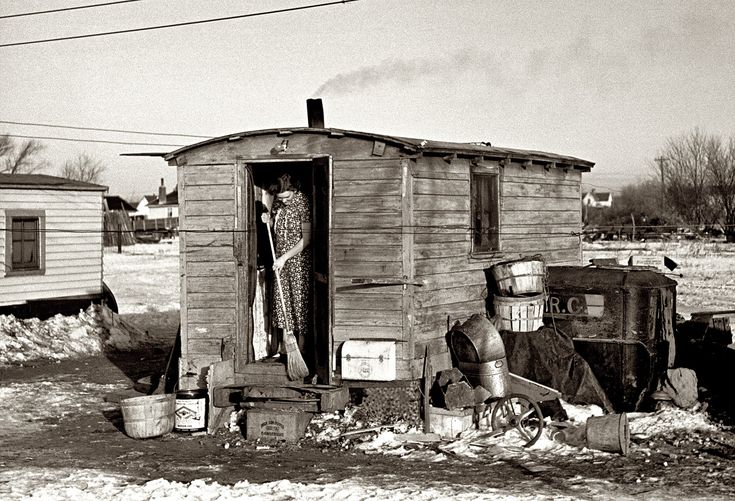 """Home Sweet Hovel: December 1936. Mrs. Charles Benning sweeping steps of shack in Shantytown. Spencer, Iowa. Seen earlier here with her baby. 35mm nitrate negative by Russell Lee for the Resettlement Administration. """"This is a cook shack that was towed by a steam tractor. The curved roof matches the canopy of the engines. Threshing crews used these for food prep and storage."""""""