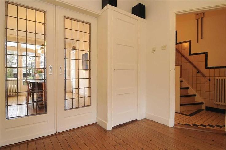 Kamer en suite deuren met kast en vieuw op de tegels in de hal van een jaren '30 huis in Haarlem