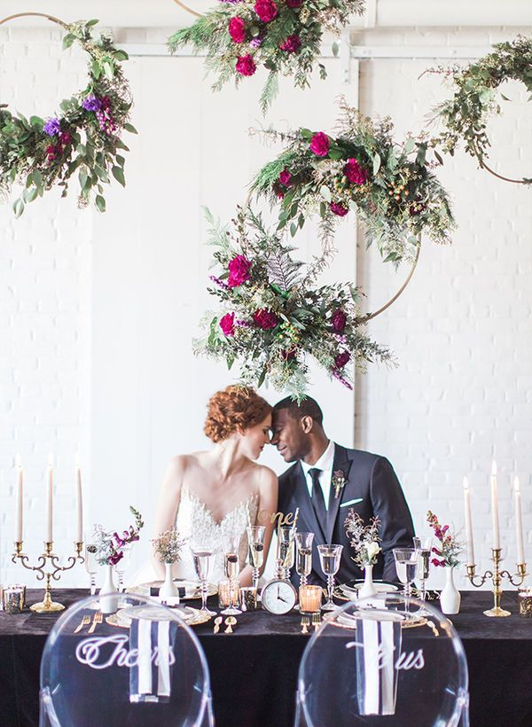 No one said that a backdrop has to be square! These suspended hoops garnished with flowers give a fresh perspective on the idea of a wedding backdrop and will quickly fill a blank space.