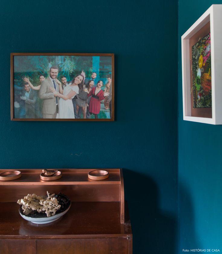 Hall de entrada de apartamento tem parede pintada de azul e escrivaninha de madeira.