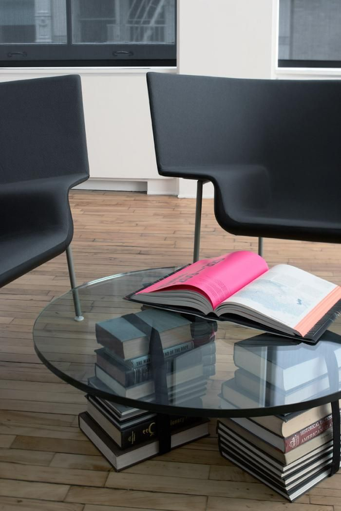 glass coffee table supported by stacked books and strapped books, Magdalena Keck