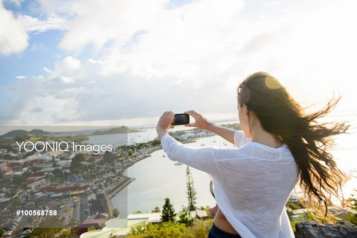 Yooniq images - Woman taking picture of coast landscape