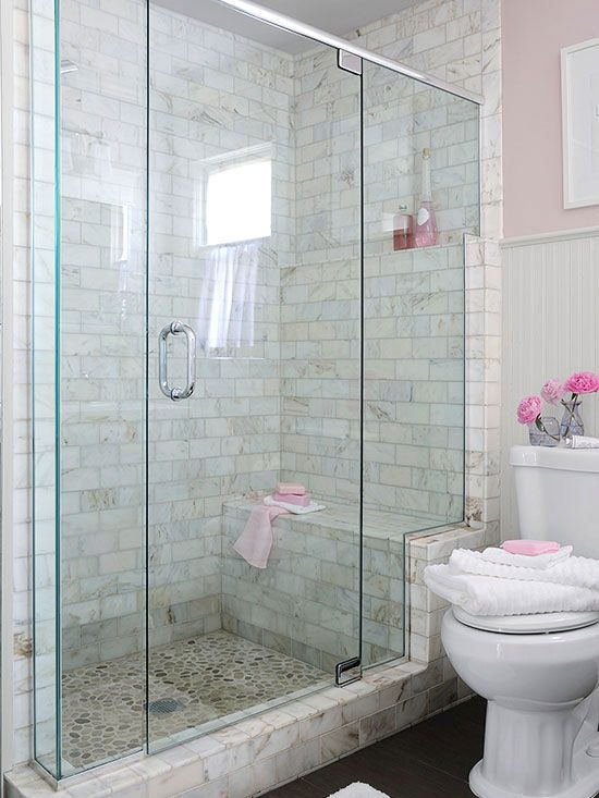 The glass enclosure stair-steps up a marble frame, highlighting the shower bench and a toiletry shelf that aligns with the beaded-board wainscoting's upper trim.