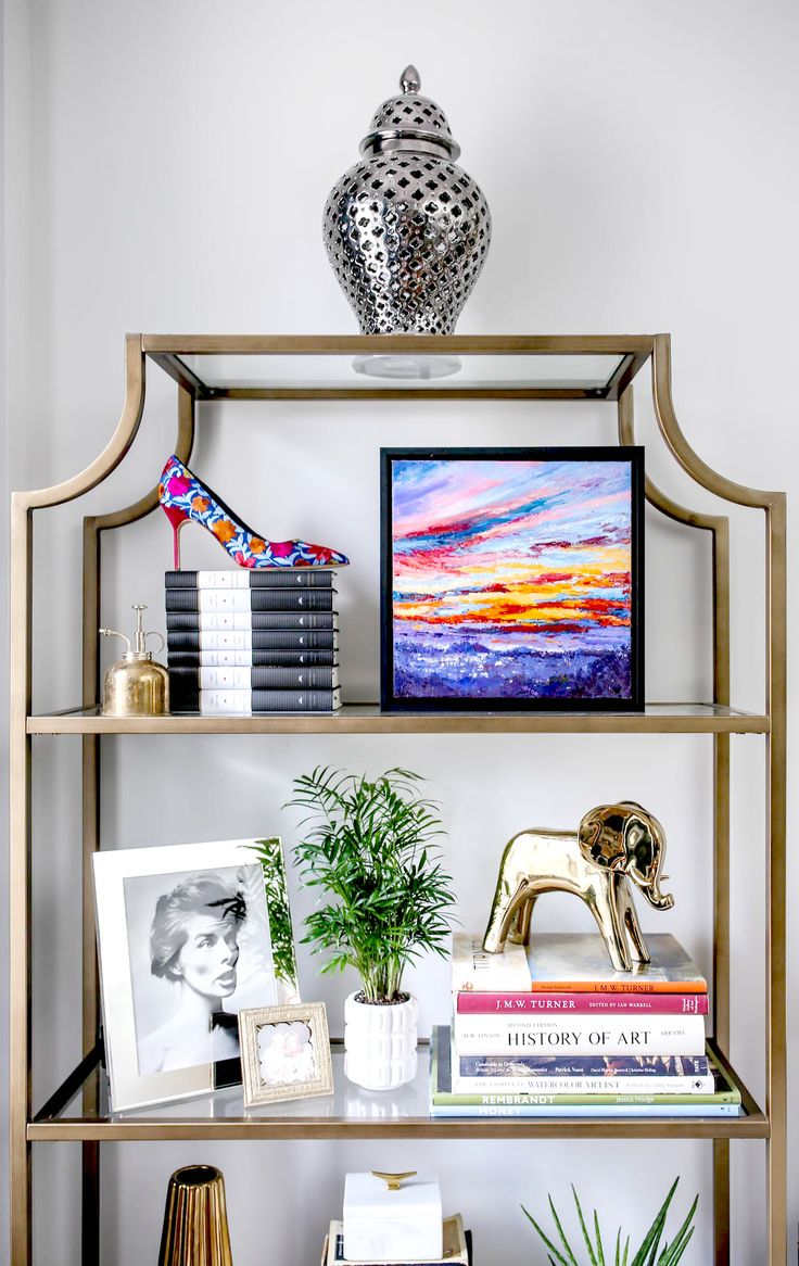 My home office! // gold brass glass etagere bookshelves, mixed metals, silver ginger jar with cut outs, jane austen books, affordable quality online art framing, elephant figurine, embroidered pumps, plant mister, mini palm, white modern planter // bookshelf styling, art deco, mid-century modern, eclectic home decor, interior design, chic style