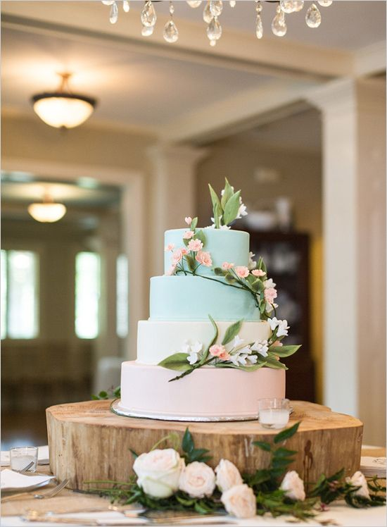 with a soft yellow cake; orange, yellow, and white flowers, with the cake topper and justa a little bits of grass around the cake topper.
