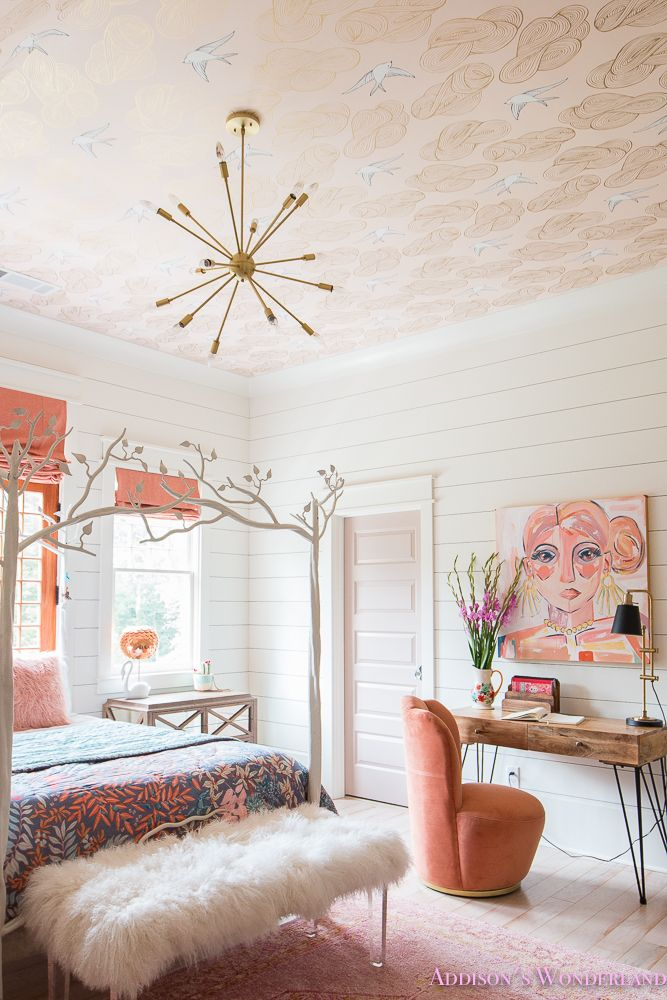 The cutest artwork for a young teen girl's bohemian bedroom! Features white shiplap walls, daydream wallpaper ceiling, orange and peach accents, bedroom desk space, roman shades over craftsman door, rose quartz doors, whitewashed hardwoods and a beautiful white tree canopy bed!