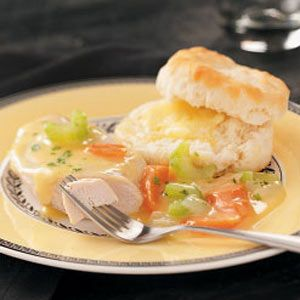 Chicken with Veggies 'n' Gravy - 3 medium carrots, chopped  2 celery ribs, chopped  1 medium onion, chopped  2 boneless skinless chicken breast halves (5 ounces each)  1/8 teaspoon pepper  1 can (10-3/4 ounces) condensed cream of chicken soup, undiluted  2/3 cup water  1/4 cup white wine or chicken broth  2 individually frozen biscuits