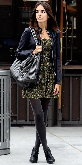 Camilla Belle wearing a little floral dress with gray tights and lace-up oxfords, topped with a leather jacket and quilted bag.