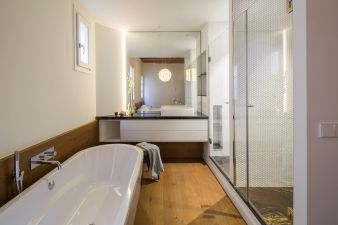 The wooden floors from the bedroom continue into the in-suite bathroom
