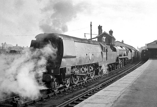 A Bulleid BB class Pacific 34051 'Winston Churchill' pauses to take water at Salisbury while hauling a train of condemned locomotives to a South Wales scrapyard. Wiltshire, UK. Negative scan.
