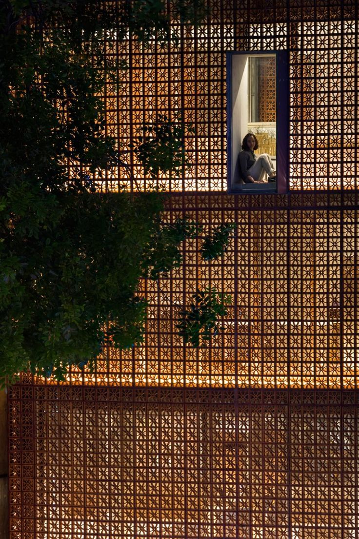 Light filters gently through the perforated terracotta facade of this showroom for electronics company Panasonic, designed by Vo Trong Nghia Architects for the Vietnamese capital Hanoi.