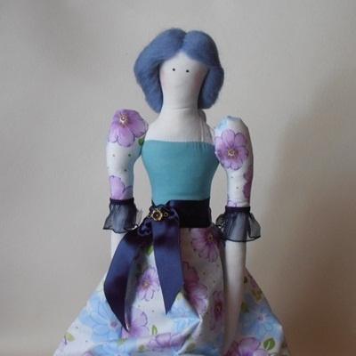 Panienka tildowa uszyta z tkaniny bawełnianej.    W środku wkład poduszkowy.    Sukieneczka niebiesko biała,przepasana satynowa wstążką z ozdobaw kolo