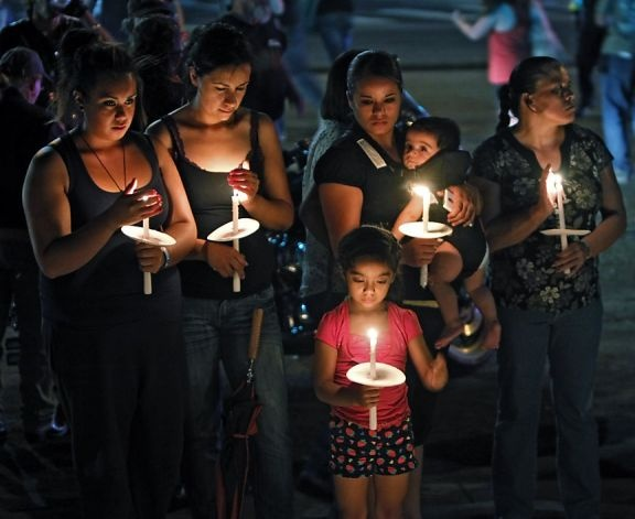 12 CO shooting victims.  People hold candles as they visit a memorial for the victims in the shooting across the street from the Century 16 movie theater in Aurora, Colo., Sunday, July 22, 2012. James Eagen Holmes has been charged in the shooting at the Aurora theater early Friday that killed twelve people and injured more than 50.He is scheduled to appear in court Monday morning. (AP Photo/Ed Andrieski) Photo: Ed Andrieski, Associated Press / SF