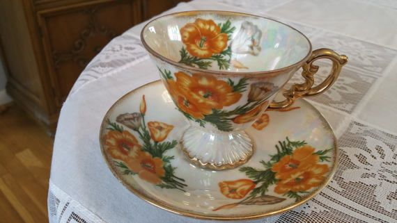 This is a gorgeous hand painted bone china tea cup and saucer set made by Ucagco, in Japan. It is part of the tea cup birthday month series, this one is August, Orange Poppy flowered. It is a white luster ware body with a orange and brown poppies, both inside and outside the cup. It has a ornate gold handle, gold trim on rim and a footed bottom with gold. There is also gold trim on saucer. It is marked August, Poppy.  Measures: Tea Cup: 3.05 tall, 3.5 rim diameter Saucer: 5.75 diameter  In…