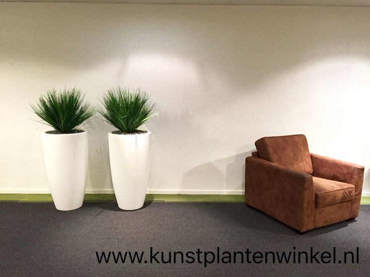 Kunst grassen in mat witte kunststof plantenbakken.
