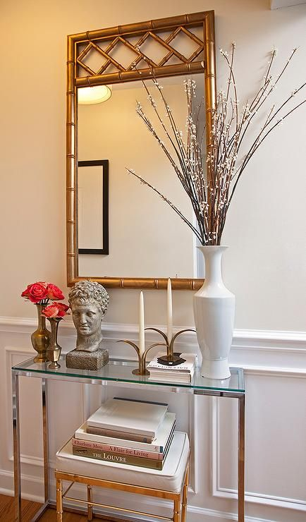 Chic foyer features upper walls painted cream and lower walls clad in wainscoting lined with a silver bamboo stool tucked under a polished nickel and glass console table as well as a gold bamboo mirror.