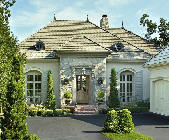 This home's grandeur relies on stately proportions in both massing and windows and a mix of warmly neutral materials