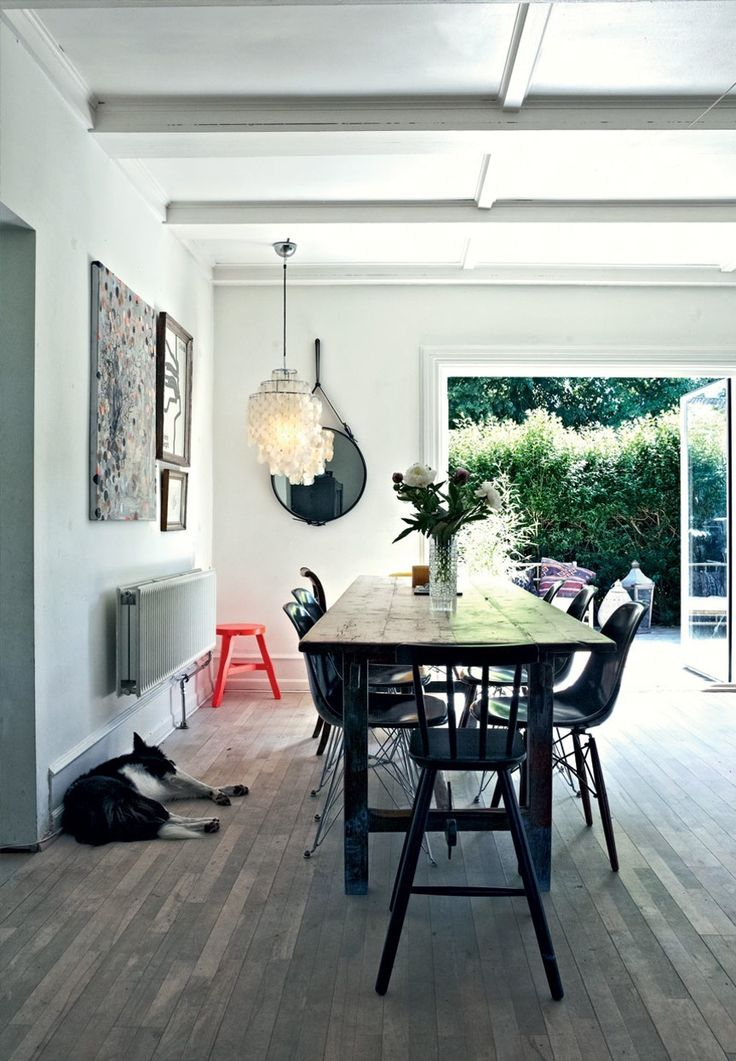 Lovely dining room with a rustic dining table surrounded by Eames chairs.