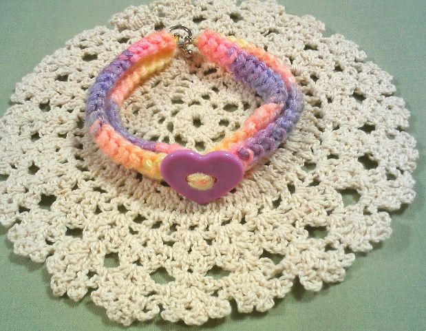 Varigated sport weight yarn have a heart bracelet.