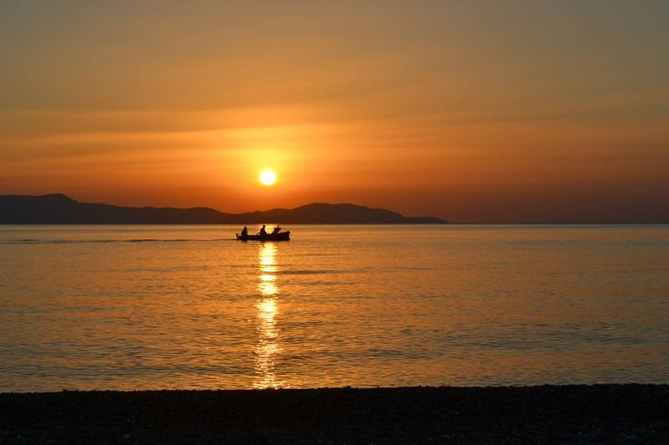 Fischermen in their boat floating on the golden line of the sunrise.... Psaropouli, Vassilika, Greece...