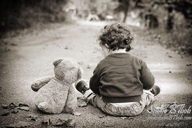 Photo d'enfant ave nounours en noir et blanc, assis.