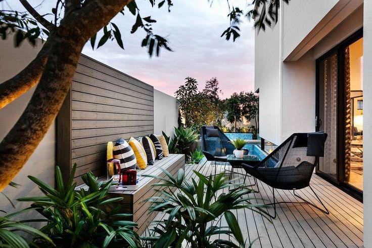 aménagement petit jardin dans l'arrière-cour - banc en bois, chaises en métal et plantes vertes