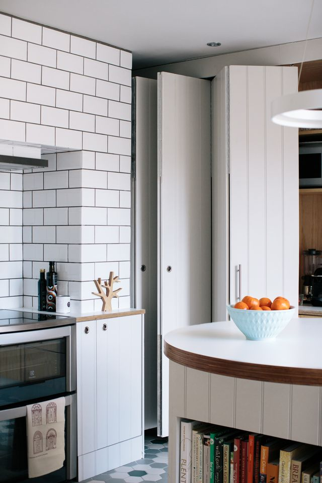 Clever concertina doors slide back to reveal open shelving, ply units and the kitchen sink.