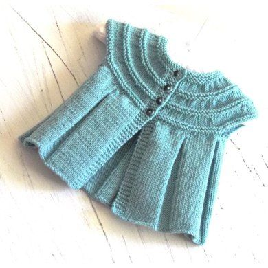 This cute little top can be knitted with or without sleeves. If knitting up the sleeveless top there is absolutely no seaming involved, if adding sleeves, the only sewing involved is the sleeve seams. A very simple knit which I would rate and easy. Would make the perfect baby shower gift.MATERIAL REQUIRED(FINE #2 Sport, Baby)(165 metres / 180 yards per 50gram ball of yarn).If knitting in Debbie Bliss Baby Cashmerino you will need to add an extra ball of yarn for all sizes.Sleeveless top…