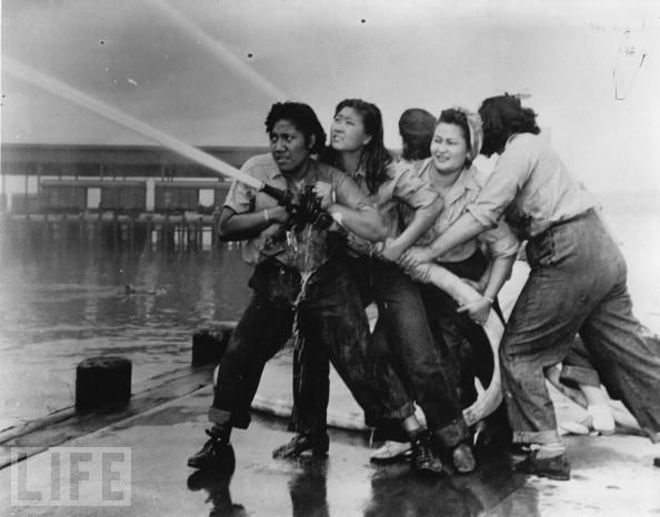 """Women firefighters douse flames at Pearl Harbor."" I love this photo, so intense."