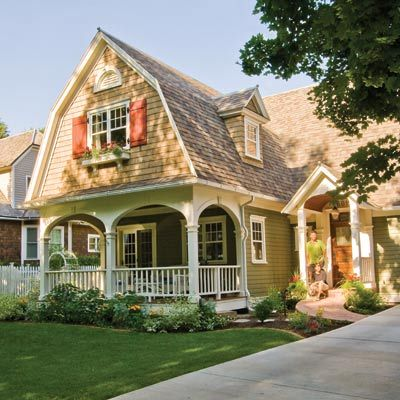 A renovated Dutch Colonial Revival with red shutters, a portico entry, and pretty porch railings | Photo: Judith Bromley | thisoldhouse.com