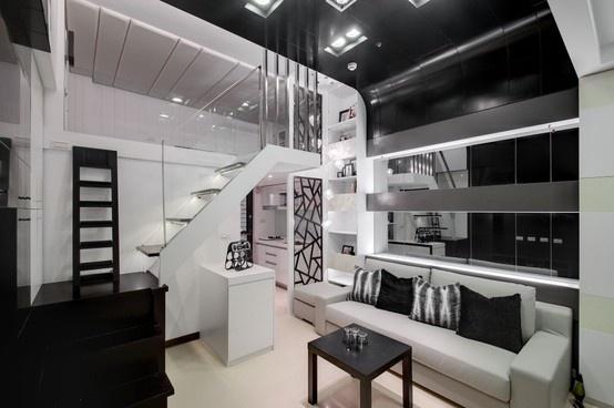 利用塑鋁板營造冷冽的科技感,並用灰鏡擴大空間感,拉長沙發背牆的造型延伸至天花板,讓挑高的感覺更加明顯。