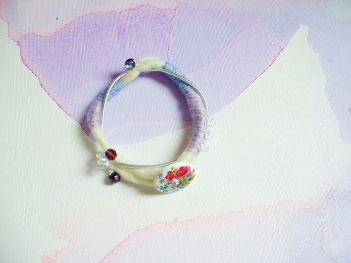 Lavender Hill Levandulový náramek z plstěného provázku, vlny, doplněn stříbrným provázkem, skleněnými korálky a dřevěným knoflíkem s růží. Vnější průměr 8,5 cm, vnitřní 6,5 cm.