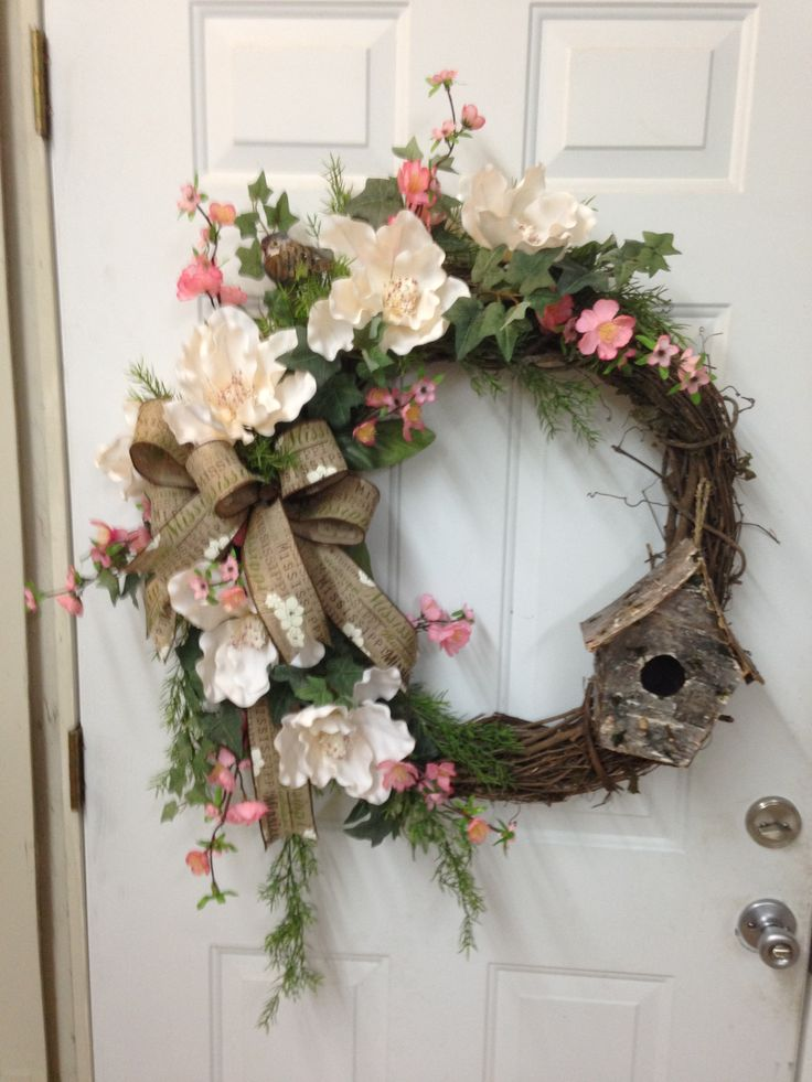 Grapevine wreath using magnolia blossoms, apple blossoms, Ivy, a bird, and birdhouse with a burlap Mississippi print bow. March 2016